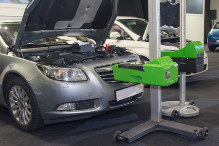Cars standing in the service station and car equipment for adjusting the headlights. Car service