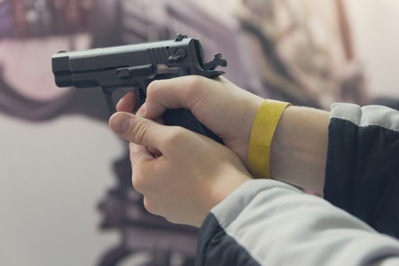 Gun in the shooter's hand close up. Weapon