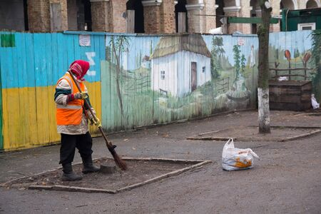Kiev, Ukraine - December 28, 2017: Woman in an orange vest cleans the street near the fence painted in the colors of the national flag