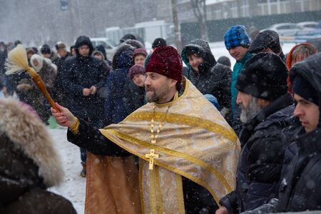 Kiev, Ukraine - January 18, 2018: Priest sprinkles the parishioners of the church with the consecrated water at the celebration of the Orthodox holiday of Baptism