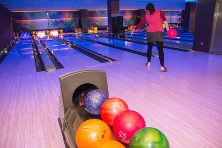 Bowling balls close up and a woman throws the ball in a bowling club Stok Fotoğraf