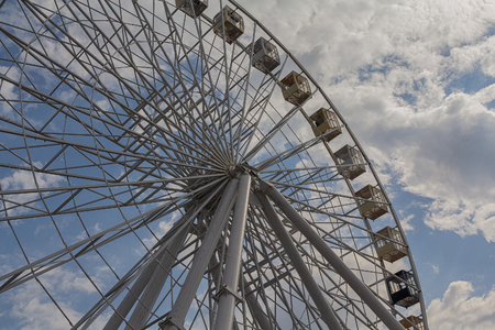 Ferris wheel on a background of blue sky and clouds