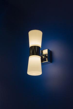 Elegant lamp sconces on the wall in the bedroom. Introrer Reklamní fotografie