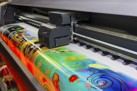 Large format printing machine in operation. Industry Stock Photo