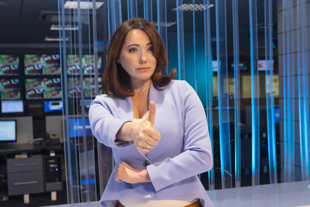 Woman with pessimistic emotion in television studio shows gesture of fingers in top