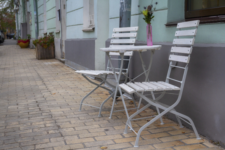 Table and chairs of street cafe on the street