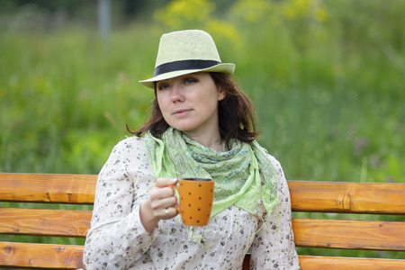 Woman in a hat and with a mug during the rest. People