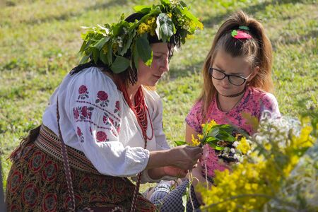 Kiev, Ukraine - July 06, 2017: Woman is training a girl to weave a wreath of flowers in celebration of the traditional Slavic holiday of Ivan Kupala