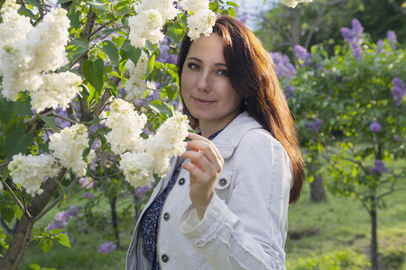 Beautiful woman in garden among the lilacs. People Stok Fotoğraf - 123963102