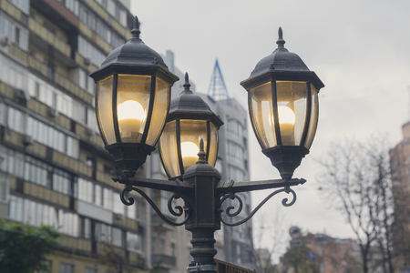 Electric light pole lantern on a city street with two bulb lamps and forged metal retro style