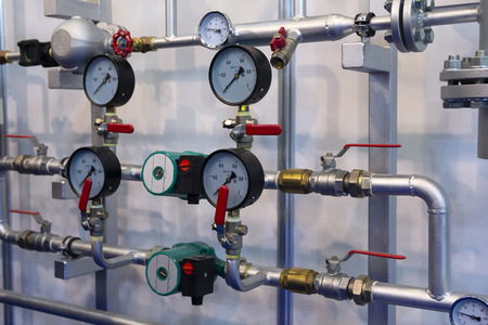 Heating system's pipes with ball valves and manometer on a grey wall