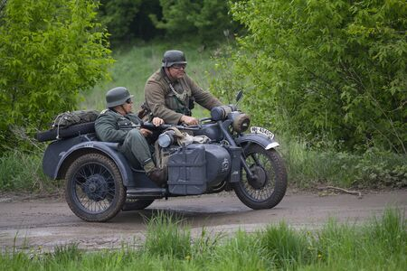 Kiev, Ukraine - May 09, 2019: Men in the clothes of German soldiers on a motorcycle at the historic reconstruction on the anniversary of the victory in the Second World War Editöryel