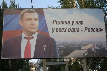 "Donetsk, Ukraine - August 02, 2018: Portrait of the former head of the Donetsk People's Republic Alexander Zakharchenko and the slogan: ""We all have the same Motherland - Russia"" in Russian on a banner in the center of the city"