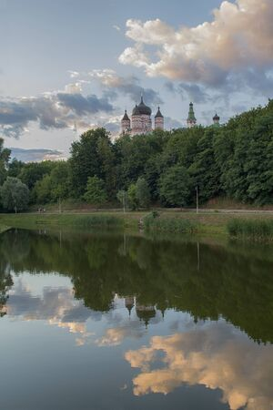 Domes of the monastery are reflected in the lake of Theophany Park. Kiev, Ukraine