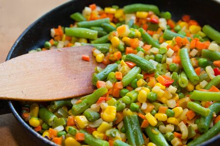 Colorful mix of vegetables is fried in a frying pan close up. Food