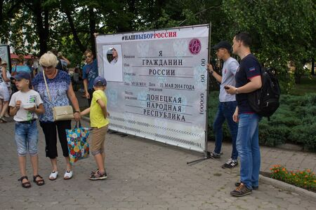 Donetsk, Ukraine - June 12, 2019: Inhabitants are photographed against the background of the stand with the passport of Russia at the celebration of the Russia Day