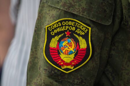 Donetsk, Ukraine - June 12, 2019: Chevron of the fighter of army of the DPR with the Soviet coat of arms and an inscription The union of the Soviet officers of the DPR in Russian
