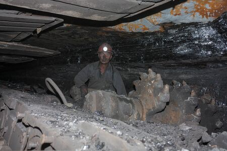 Donetsk, Ukraine - August, 16, 2013: Miner near the coal mining shearer. Mine is named Chelyuskintsev