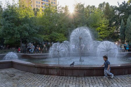 Donetsk, Ukraine - August 28, 2018: People rest near the fountain on the evening of the summer day