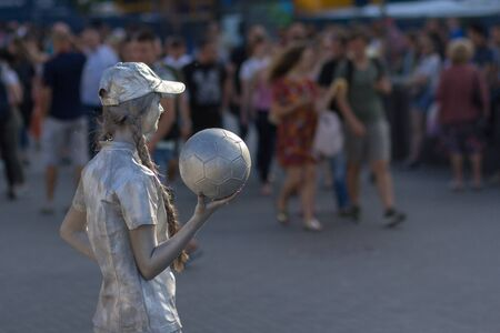 Kiev, Ukraine - May 25, 2018: Girl - live statues with a soccer ball entertains for tourists on the eve of the Champions League f