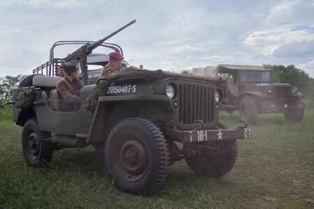 Kiev, Ukraine - May 09, 2018: Mens and a boy in the form of American soldiers and an American army jeep at a historical reconstruction to celebrate the anniversary of victory in World War II