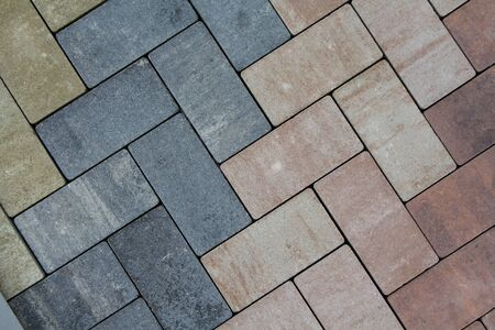 Multicolored paving slabs for road paving by mosaic on shop window. Construction