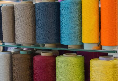 Bobbins with multicolored threads for sewing. Fabric and textile industry Banco de Imagens