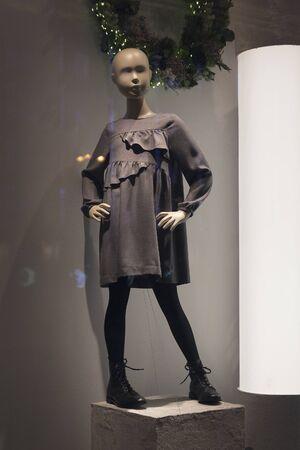 Children's mannequin in a dress in a shop window. Fashion