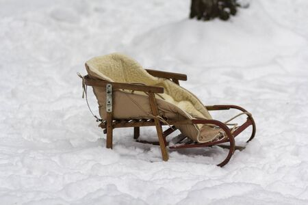 Retro wooden sleigh in the snow in the park Stock Photo