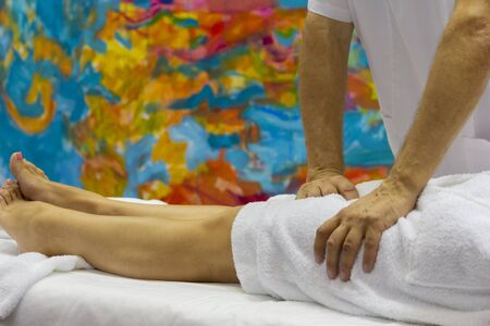 Hands of the masseur and the client's feet during a massage treatment. Medicine