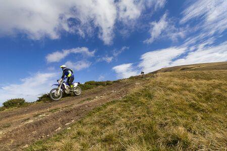 Enduro biker crossing road at high speed in mountains. Carpathian