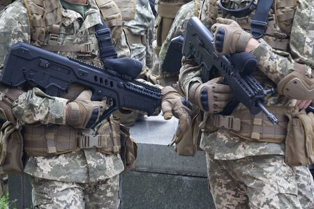 Automatic rifles in the hands of soldiers close up. Weaponry Stock fotó
