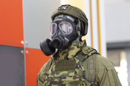 Mannequin head in gas mask and chemical protective suit made of special fabric in marking green Imagens