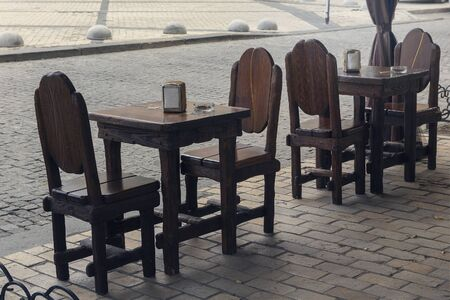 Wooden tables and chairs in a retro style street cafe without people