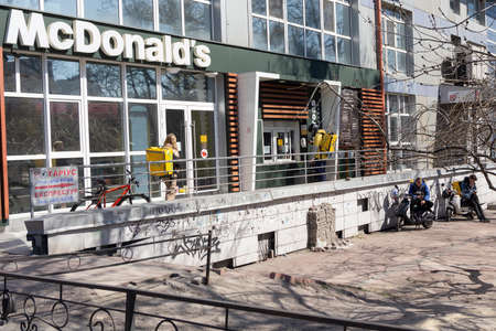 Kiev, Ukraine -April 06, 2020: Couriers and delivery services Glovo in the queue near the McDonald's. Ukraine stops bars, restaurants and shopping centers, to stop the spread of the coronavirus.