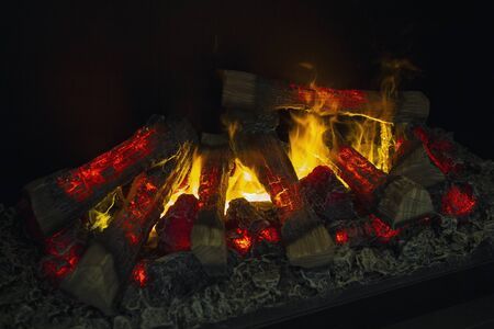 Bright fire burns in a fireplace. Homeliness
