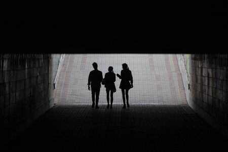 Silhouettes of young people in the underpass. Peoples