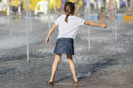 Children bathe in the fountain in hot summer day