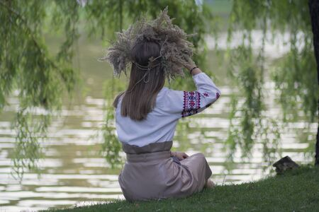 Girl in a grass wreath sits by the lake. National Slavic holiday of Ivan Kupala