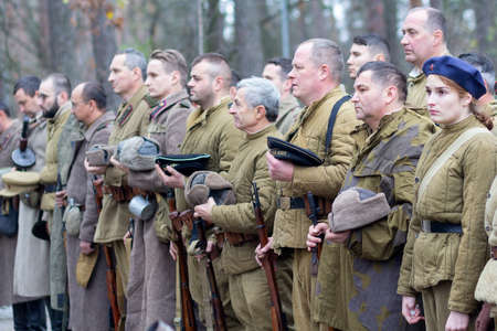Vorzel, Ukraine - November 03, 2019: People in the form of Red Army soldiers stand in formation with weapons on the historical reconstruction of the anniversary of the victory in World War II