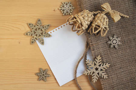 Snowflakes and bells on a wooden surface. Christmas decorations 免版税图像