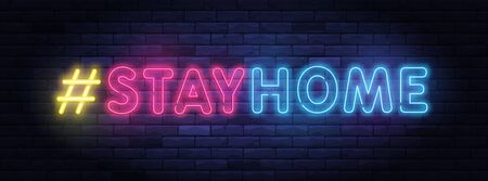 Stay home hashtag in neon style. Coronavirus pandemic protection and prevention effort. Social activity message. Self-isolation and quarantine. To stay at home brightly illuminated neon sign on wall.