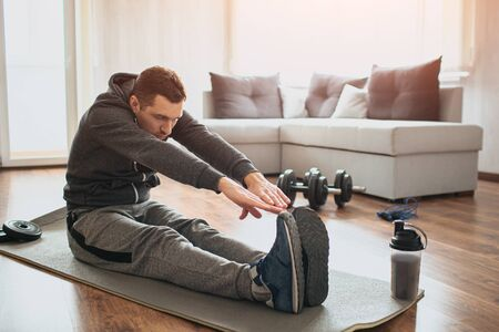 Young ordinary man go in for sport at home. Beginner or amateur in workout activity sit on mat and stretch to his toes. Hardworking guy exercising in apatment alone.