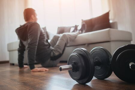 Young ordinary man go in for sport at home. Hardworking beginner sit on floor and hold legs on sofa. Freshmen trying to do abs exercising. Home alone doing workout. Dumbbells on floor.