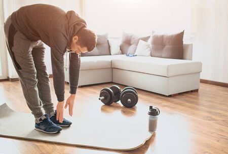 Young ordinary man go in for sport at home. Stand on mat and stretch down to toes. Ordinary guy warming out body before exercise. Working out alone in middle of room. Sport ewuipment on floor. Foto de archivo