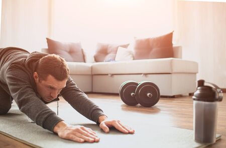 Young ordinary man go in for sport at home. Cut view of beginner guy stretching his body and pull hands foward on mat. Improving body shape. Real man with no knowledge in sport start workout. Foto de archivo