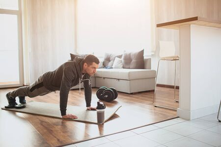 Young ordinary man go in for sport at home. Full size picture of regular ordinary guy stand in plank position alone in room. Beginner try to do his best and exercise. Hardworking real person. Foto de archivo