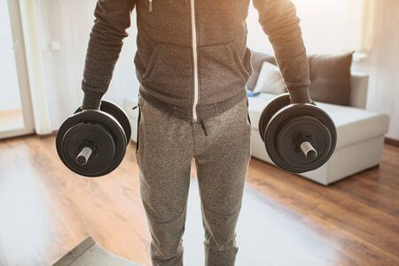 Young ordinary man go in for sport at home. Cut view of guys low part of body. Freshman and sport beginner hold two dumbbells in hands and stay straight. Ordinary man ready to start his workout.