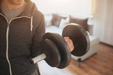 Young ordinary man go in for sport at home. Real picture of not strong guy hold up dumbbells in hand. Trying to do his muscles stronger. Ordinary man with no experience in training. Beginner. Foto de archivo