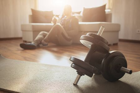 Young ordinary man go in for sport at home. Regular guy sit at sofa on floor after hard workout. Has rest and drink water. Blurred sunny background. Pair of dumbbells lying on mat in front. Foto de archivo